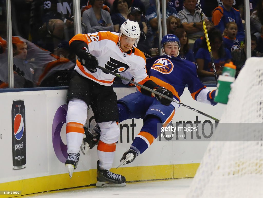 Kyle Burroughs #40 of the New York Islanders is hit into the boards by Michael Raffl #12 of the Philadelphia Flyers during the second period during a preseason game at the Nassau Veterans Memorial Coliseum on September 17, 2017 in Uniondale, New York.