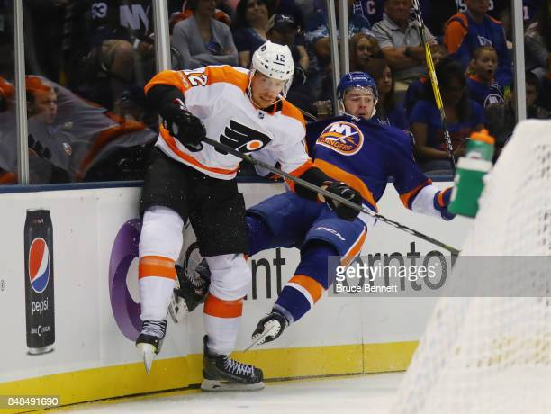 Kyle Burroughs of the New York Islanders is hit into the boards by Michael Raffl of the Philadelphia Flyers during the second period during a...