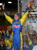 Kyle Busch driver of the Hendrick Motorsports Kellogg's Chevrolet celebrates winning the NASCAR Nextel Cup Series Sony HD 500 on September 4 2005 at...