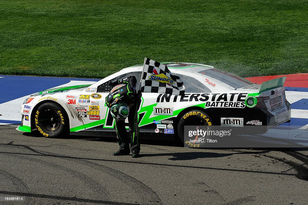 Kyle Busch, driver of the #18 Interstate Batteries Toyota, bows to the crowd with the checkered flag after winning the NASCAR Sprint Cup Series Auto Club 400 at Auto Club Speedway on March 24, 2013 in Fontana, California.