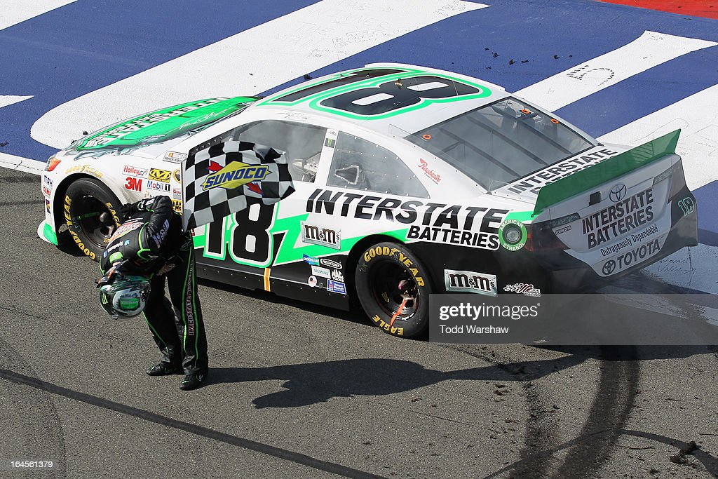 Kyle Busch, driver of the #18 Interstate Batteries Toyota, bows towards the stands with the checkered flag after winning the NASCAR Sprint Cup Series Auto Club 400 at Auto Club Speedway on March 24, 2013 in Fontana, California.