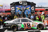 Kyle Busch driver of the Interstate Batteries Toyota celebrates in Victory Lane after winning the NASCAR Sprint Cup Series Auto Club 400 at Auto Club...