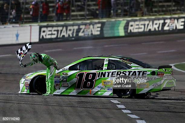 Kyle Busch driver of the Interstate Batteries Toyota celebrates winning the NASCAR Sprint Cup Series Duck Commander 500 at Texas Motor Speedway on...