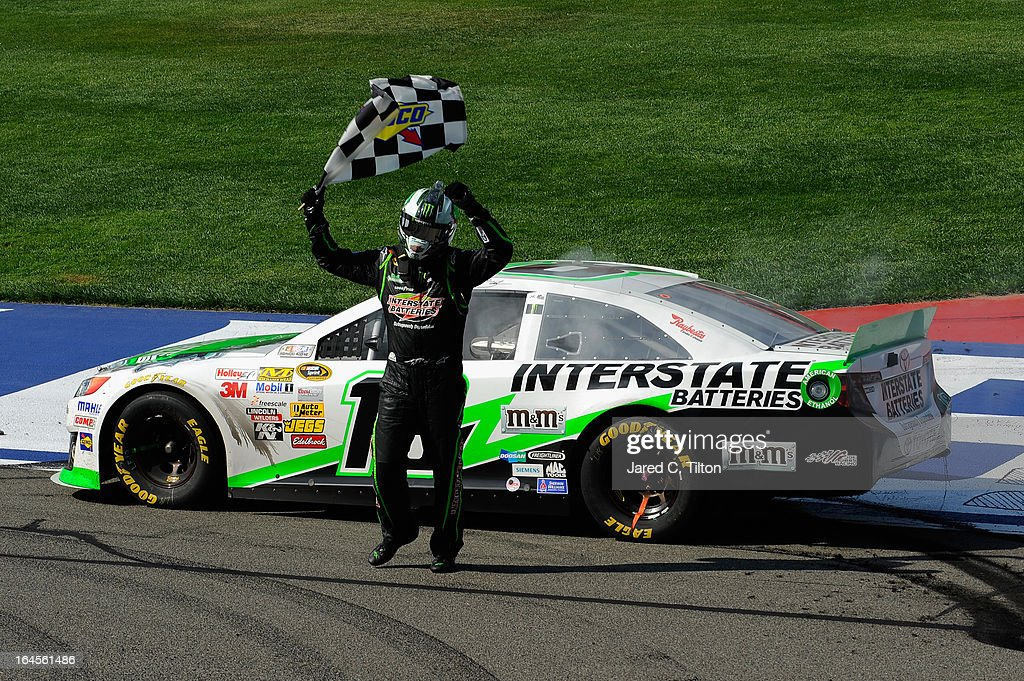 Kyle Busch, driver of the #18 Interstate Batteries Toyota, celebrates with the checkered flag after winning the NASCAR Sprint Cup Series Auto Club 400 at Auto Club Speedway on March 24, 2013 in Fontana, California.