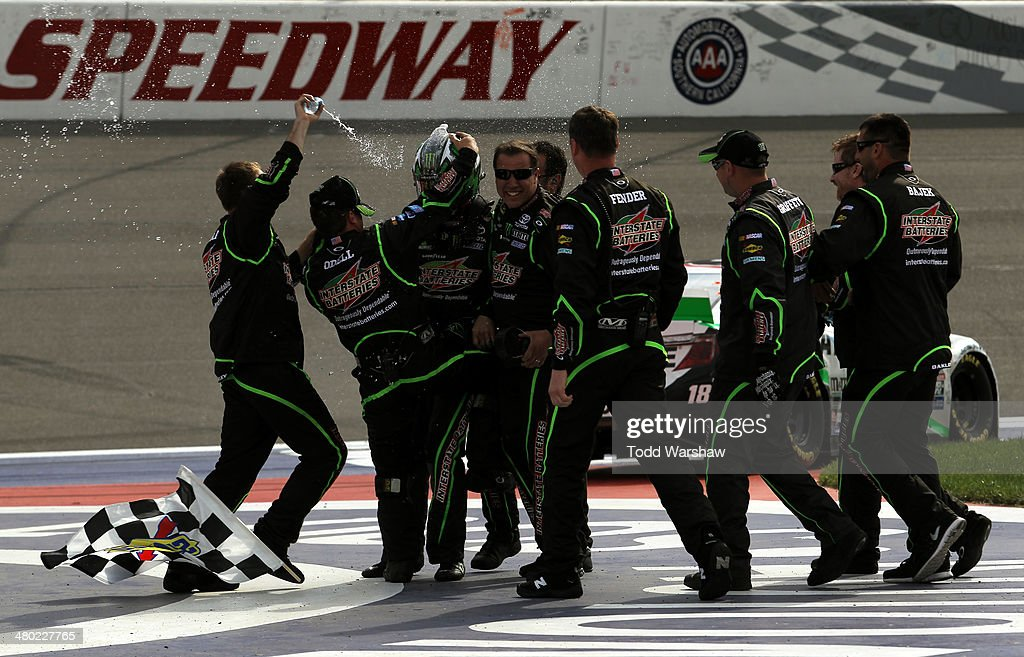 Kyle Busch driver of the Interstate Batteries Toyota celebrates with his teammates after winning the NASCAR Sprint Cup Series Auto Club 400 at Auto...