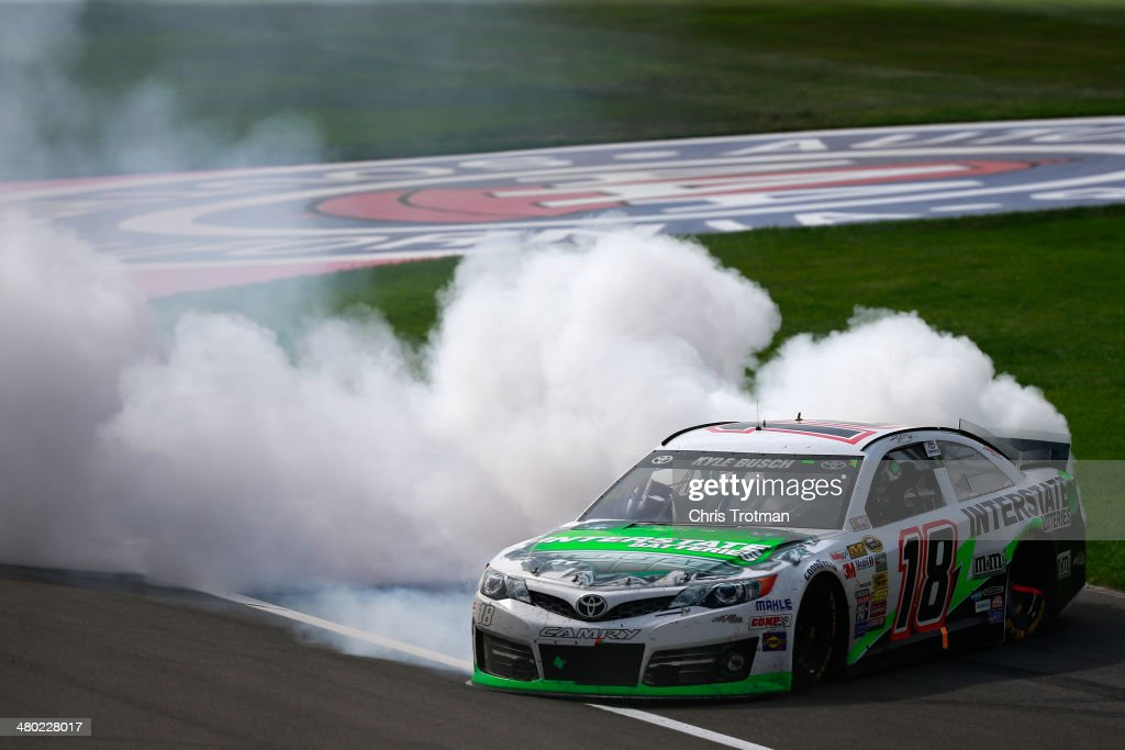 <a gi-track='captionPersonalityLinkClicked' href=/galleries/search?phrase=Kyle+Busch&family=editorial&specificpeople=211123 ng-click='$event.stopPropagation()'>Kyle Busch</a>, driver of the #18 Interstate Batteries Toyota, celebrates with a burnout after winning the NASCAR Sprint Cup Series Auto Club 400 at Auto Club Speedway on March 23, 2014 in Fontana, California.