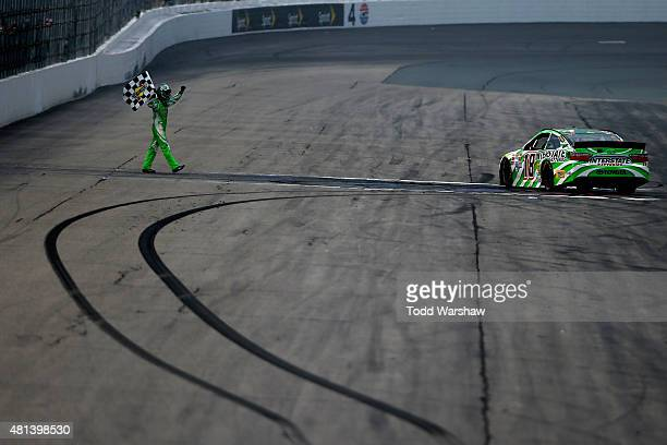 Kyle Busch driver of the Interstate Batteries Toyota celebrates with the checkered flag after winning the NASCAR Sprint Cup Series 5Hour ENERGY 301...