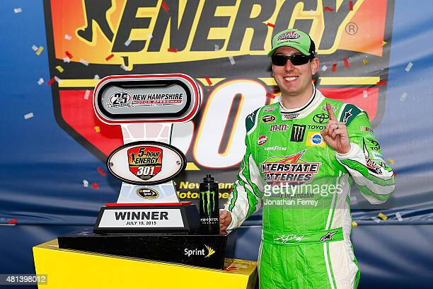 Kyle Busch driver of the Interstate Batteries Toyota poses in Victory Lane after winning the NASCAR Sprint Cup Series 5Hour ENERGY 301 at New...
