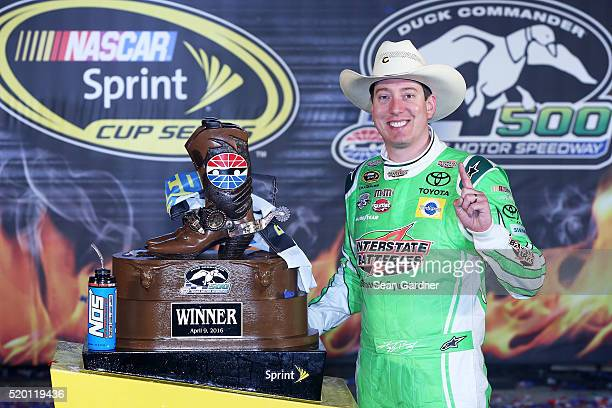 Kyle Busch driver of the Interstate Batteries Toyota poses in Victory Lane after winning the NASCAR Sprint Cup Series Duck Commander 500 at Texas...