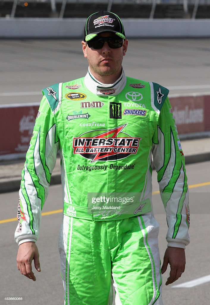 Kyle Busch, driver of the #18 Interstate Batteries Toyota, stands on the grid during qualifying for the NASCAR Sprint Cup Series Pure Michigan 400 at Michigan International Speedway on August 15, 2014 in Brooklyn, Michigan.