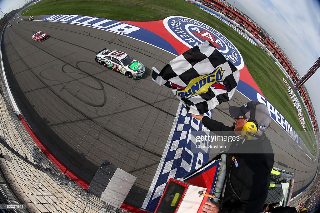 Kyle Busch driver of the Interstate Batteries Toyota takes the checkered flag to win the NASCAR Sprint Cup Series Auto Club 400 at Auto Club Speedway...