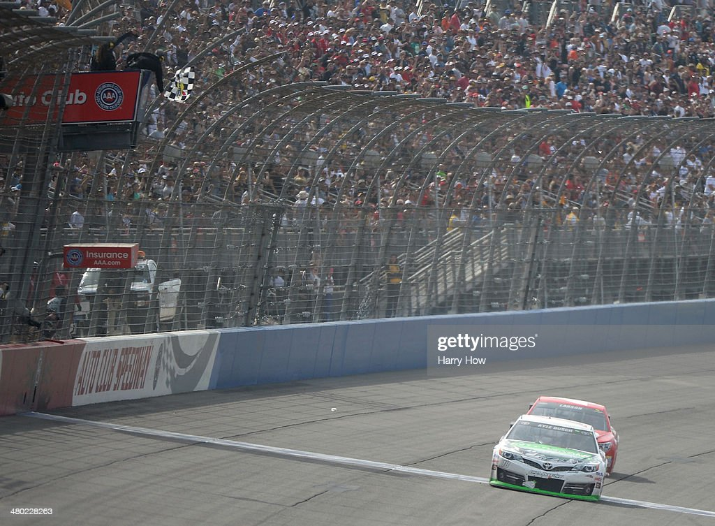 <a gi-track='captionPersonalityLinkClicked' href=/galleries/search?phrase=Kyle+Busch&family=editorial&specificpeople=211123 ng-click='$event.stopPropagation()'>Kyle Busch</a>, driver of the #18 Interstate Batteries Toyota, takes the checkered flag ahead of <a gi-track='captionPersonalityLinkClicked' href=/galleries/search?phrase=Kyle+Larson+-+Race+Car+Driver&family=editorial&specificpeople=2115989 ng-click='$event.stopPropagation()'>Kyle Larson</a>, driver of the #42 Target Chevrolet, to win the NASCAR Sprint Cup Series Auto Club 400 at Auto Club Speedway on March 23, 2014 in Fontana, California.