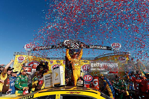 Kyle Busch driver of the MM's 75th Anniversary Toyota celebrates in Victory Lane after winning the NASCAR Sprint Cup Series STP 500 at Martinsville...