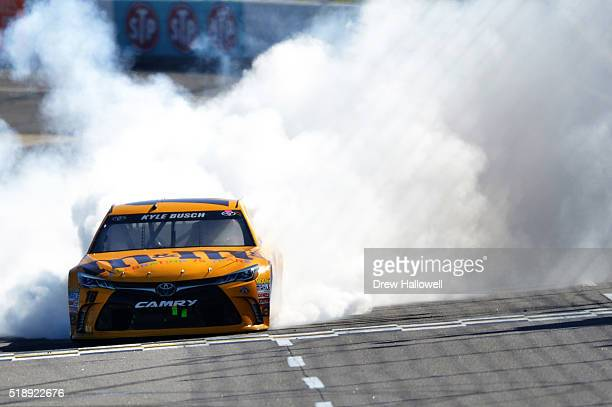 Kyle Busch driver of the MM's 75th Anniversary Toyota celebrates with a burnout after winning the NASCAR Sprint Cup Series STP 500 at Martinsville...
