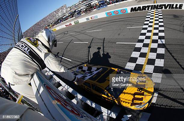 Kyle Busch driver of the MM's 75th Anniversary Toyota crosses the finish line to win the NASCAR Sprint Cup Series STP 500 at Martinsville Speedway on...