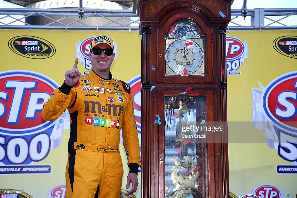 Kyle Busch, driver of the #18 M&M's 75th Anniversary Toyota, poses for a photo in Victory Lane ater winning the NASCAR Sprint Cup Series STP 500 at Martinsville Speedway on April 3, 2016 in Martinsville, Virginia.