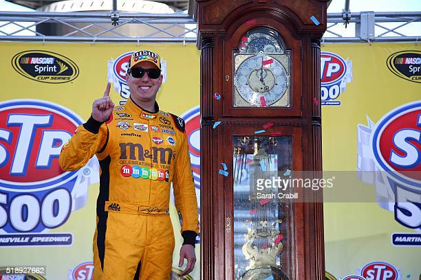 Kyle Busch driver of the MM's 75th Anniversary Toyota poses for a photo in Victory Lane ater winning the NASCAR Sprint Cup Series STP 500 at...
