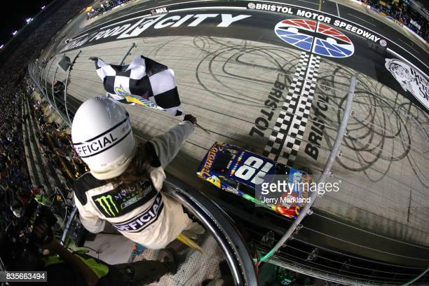 Kyle Busch driver of the MM's Caramel Toyota takes the checkered flag to win the Monster Energy NASCAR Cup Series Bass Pro Shops NRA Night Race at...