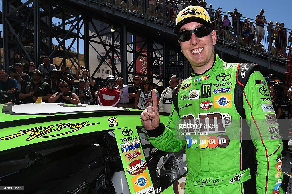 Kyle Busch driver of the MM's Crispy Toyota celebrates by putting the Winner's sticker on his car after winning the NASCAR Sprint Cup Series...