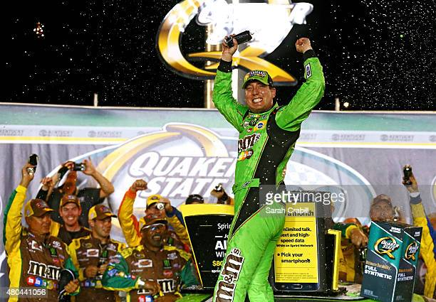 Kyle Busch driver of the MM's Crispy Toyota celebrates in Victory Lane after winning the NASCAR Sprint Cup Series Quaker State 400 presented by...
