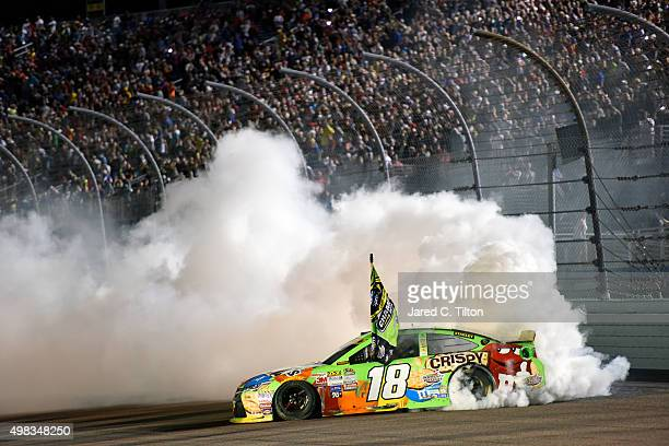 Kyle Busch driver of the MM's Crispy Toyota celebrates winning the series championship and the race with a burnout after the NASCAR Sprint Cup Series...