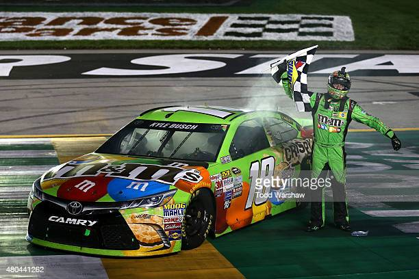 Kyle Busch driver of the MM's Crispy Toyota celebrates with the checkered flag after winning the NASCAR Sprint Cup Series Quaker State 400 presented...