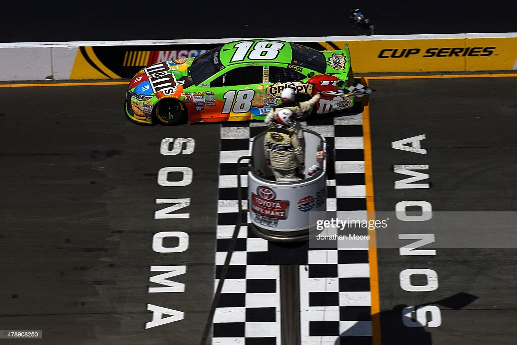 Kyle Busch driver of the MM's Crispy Toyota crosses the finish line to win the NASCAR Sprint Cup Series Toyota/Save Mart 350 at Sonoma Raceway on...