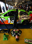 Kyle Busch driver of the MM's Crispy Toyota lies on the garage floor during a rain delay in practice for the NASCAR Sprint Cup Series Quaker State...