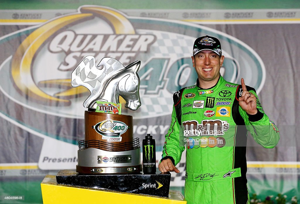 Kyle Busch, driver of the #18 M&M's Crispy Toyota, poses with the winner's trophy in Victory Lane after winning the NASCAR Sprint Cup Series Quaker State 400 presented by Advance Auto Parts at Kentucky Speedway on July 11, 2015 in Sparta, Kentucky.