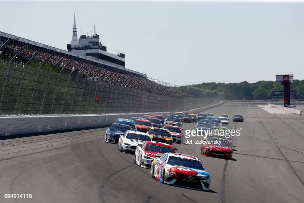 Kyle Busch driver of the MM's Red White Blue Toyota leads the field to turn one after taking the green flag to start the Monster Energy NASCAR Cup...