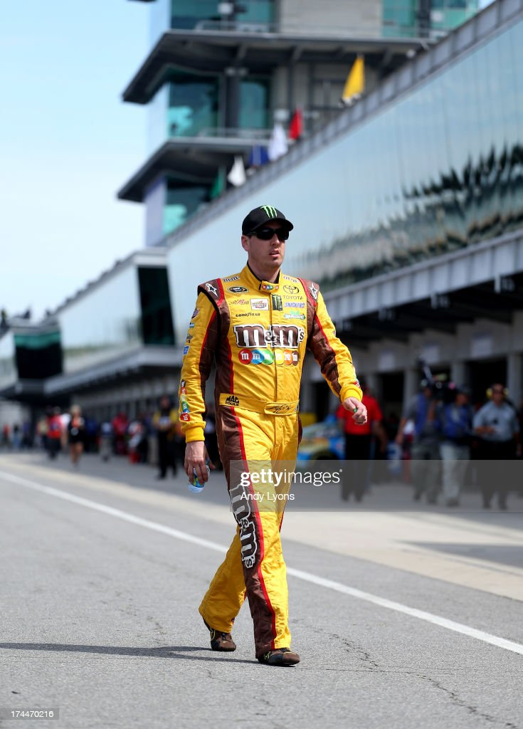 <a gi-track='captionPersonalityLinkClicked' href=/galleries/search?phrase=Kyle+Busch&family=editorial&specificpeople=211123 ng-click='$event.stopPropagation()'>Kyle Busch</a>, driver of the #18 M&M's Red-White-Blue M-Prove America Toyota, walks in the garage area during practice for the NASCAR Sprint Cup Series Samuel Deeds 400 At The Brickyard at Indianapolis Motor Speedway on July 26, 2013 in Indianapolis, Indiana.