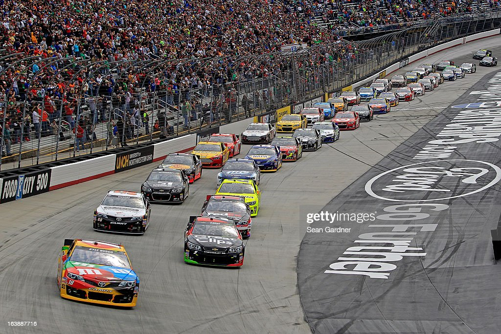 Kyle Busch, driver of the #18 M&M's Toyota, and Kasey Kahne, driver of the #5 Great Clips Chevrolet, lead the field to start the NASCAR Sprint Cup Series Food City 500 at Bristol Motor Speedway on March 17, 2013 in Bristol, Tennessee.