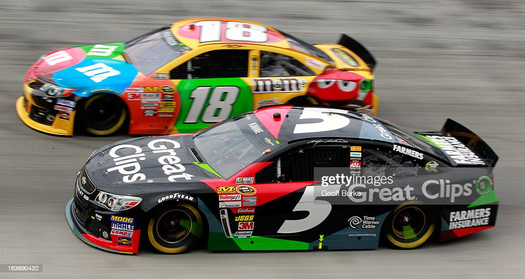 Kyle Busch, driver of the #18 M&M's Toyota, and Kasey Kahne, driver of the #5 Great Clips Chevrolet, race side by side during the NASCAR Sprint Cup Series Food City 500 at Bristol Motor Speedway on March 17, 2013 in Bristol, Tennessee.