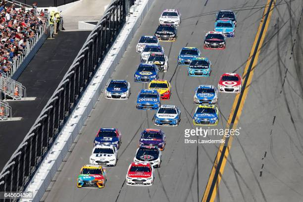 Kyle Busch driver of the MM's Toyota and Ryan Blaney driver of the Motorcraft/Quick Lane Tire Auto Center Ford lead a pack of cars during the 59th...