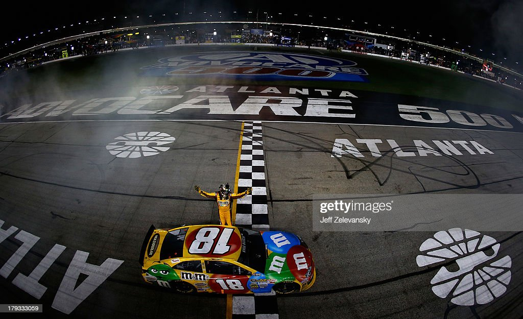 <a gi-track='captionPersonalityLinkClicked' href=/galleries/search?phrase=Kyle+Busch&family=editorial&specificpeople=211123 ng-click='$event.stopPropagation()'>Kyle Busch</a>, driver of the #18 M&M's Toyota, celebrates after winning the NASCAR Sprint Cup Series AdvoCare 500 at Atlanta Motor Speedway on September 1, 2013 in Hampton, Georgia.