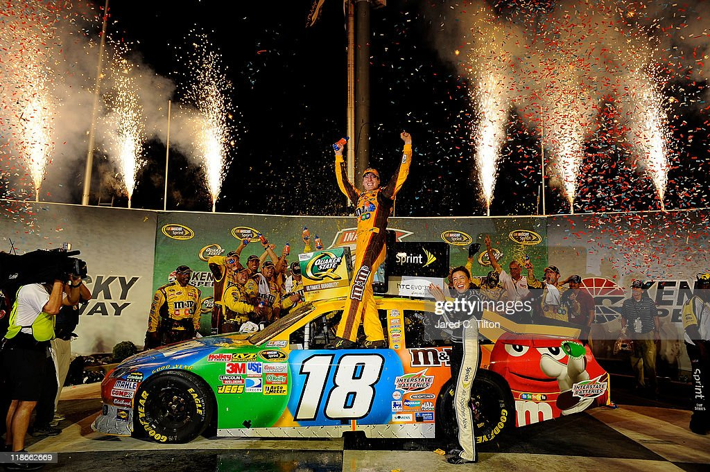 <a gi-track='captionPersonalityLinkClicked' href=/galleries/search?phrase=Kyle+Busch&family=editorial&specificpeople=211123 ng-click='$event.stopPropagation()'>Kyle Busch</a>, driver of the #18 M&M's Toyota, celebrates in Victory Lane after winning the NASCAR Sprint Cup Series Quaker State 400 at Kentucky Speedway on July 9, 2011 in Sparta, Kentucky.