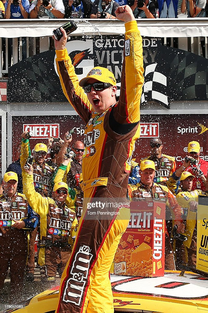 Kyle Busch, driver of the #18 M&M's Toyota, celebrates in Victory Lane after winning the NASCAR Sprint Cup Series Cheez-It 355 at The Glen at Watkins Glen International on August 11, 2013 in Watkins Glen, New York.