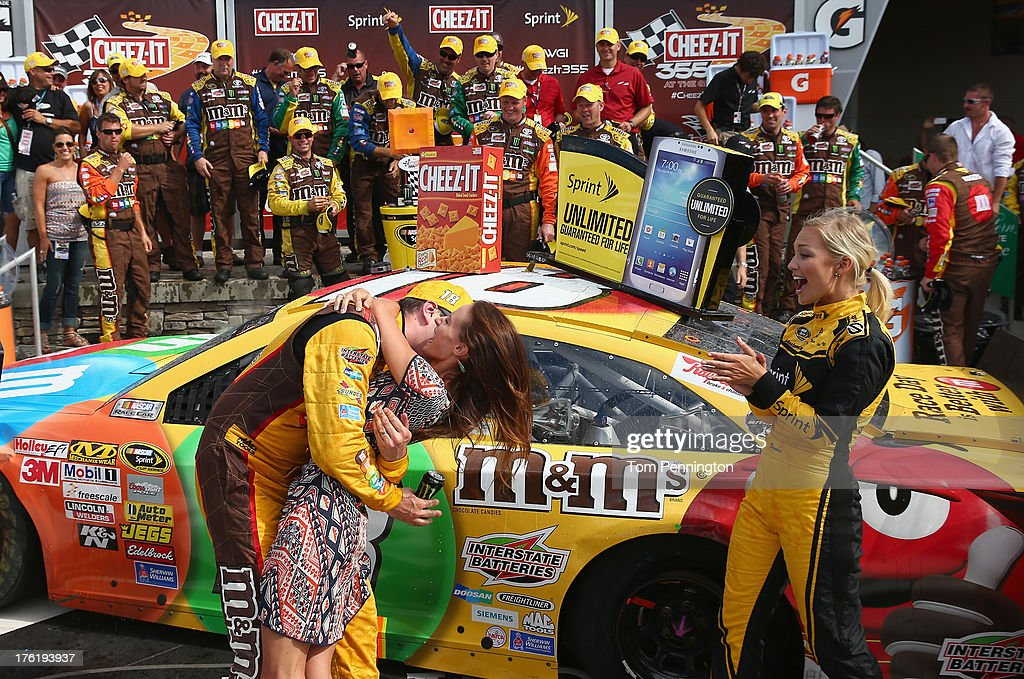 Kyle Busch, driver of the #18 M&M's Toyota, celebrates in Victory Lane with wife Samantha Busch after winning during the NASCAR Sprint Cup Series Cheez-It 355 at The Glen at Watkins Glen International on August 11, 2013 in Watkins Glen, New York.
