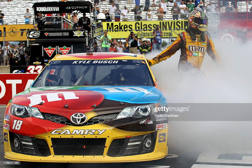 <a gi-track='captionPersonalityLinkClicked' href=/galleries/search?phrase=Kyle+Busch&family=editorial&specificpeople=211123 ng-click='$event.stopPropagation()'>Kyle Busch</a>, driver of the #18 M&M's Toyota, celebrates with a burnout after winning the NASCAR Sprint Cup Series Cheez-It 355 at The Glen at Watkins Glen International on August 11, 2013 in Watkins Glen, New York.