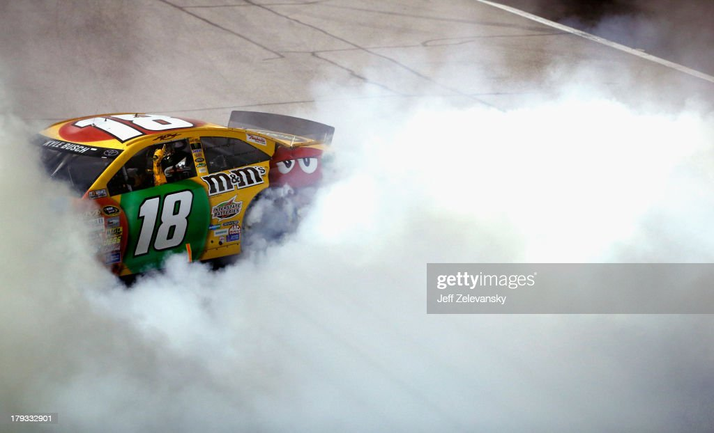 <a gi-track='captionPersonalityLinkClicked' href=/galleries/search?phrase=Kyle+Busch&family=editorial&specificpeople=211123 ng-click='$event.stopPropagation()'>Kyle Busch</a>, driver of the #18 M&M's Toyota, celebrates with a burnout after winning the NASCAR Sprint Cup Series AdvoCare 500 at Atlanta Motor Speedway on September 1, 2013 in Hampton, Georgia.