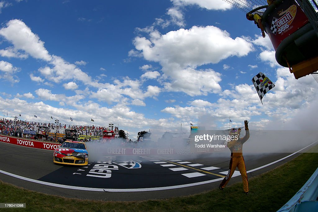 Kyle Busch, driver of the #18 M&M's Toyota, celebrates with a burnout and the checkered flag after winning the NASCAR Sprint Cup Series Cheez-It 355 at The Glen at Watkins Glen International on August 11, 2013 in Watkins Glen, New York.