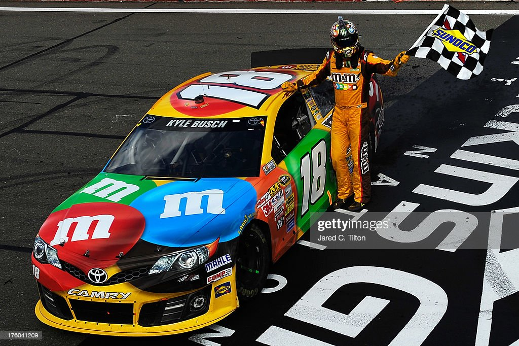 <a gi-track='captionPersonalityLinkClicked' href=/galleries/search?phrase=Kyle+Busch&family=editorial&specificpeople=211123 ng-click='$event.stopPropagation()'>Kyle Busch</a>, driver of the #18 M&M's Toyota, celebrates with the checkered flag after winning the NASCAR Sprint Cup Series Cheez-It 355 at The Glen at Watkins Glen International on August 11, 2013 in Watkins Glen, New York.