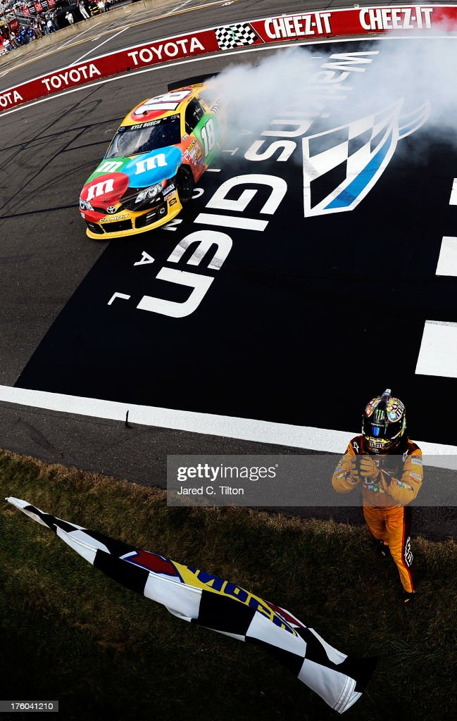 Kyle Busch, driver of the #18 M&M's Toyota, celebrates with the checkered flag after winning the NASCAR Sprint Cup Series Cheez-It 355 at The Glen at Watkins Glen International on August 11, 2013 in Watkins Glen, New York.