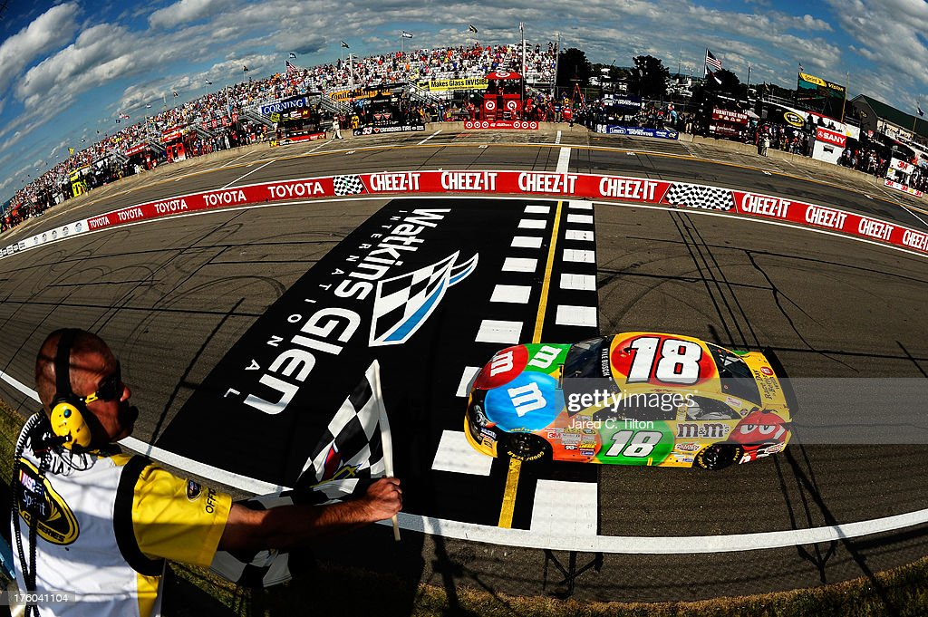<a gi-track='captionPersonalityLinkClicked' href=/galleries/search?phrase=Kyle+Busch&family=editorial&specificpeople=211123 ng-click='$event.stopPropagation()'>Kyle Busch</a>, driver of the #18 M&M's Toyota, crosses the finish line to win the NASCAR Sprint Cup Series Cheez-It 355 at The Glen at Watkins Glen International on August 11, 2013 in Watkins Glen, New York.