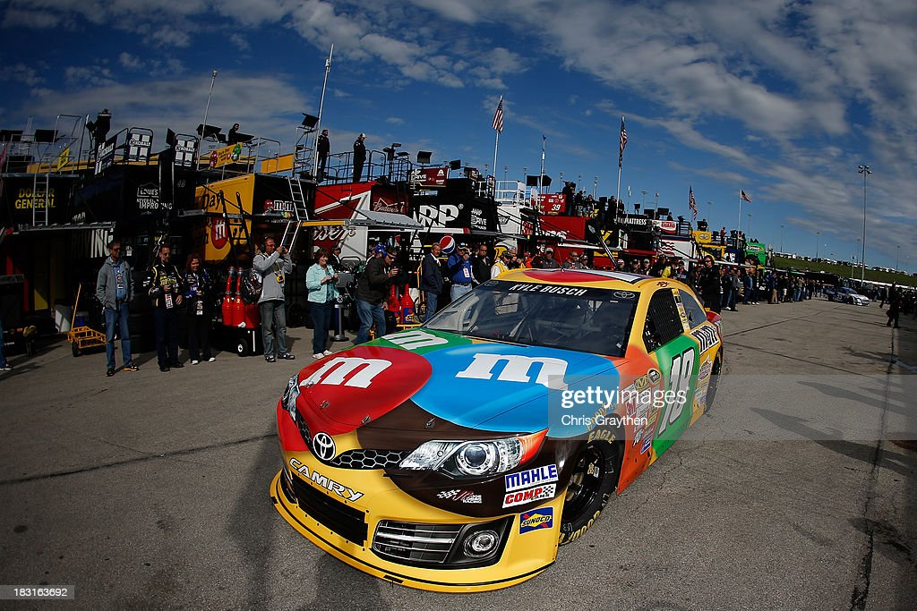 Kyle Busch, driver of the #18 M&M's Toyota, drives through the garage area during practice for the NASCAR Sprint Cup Series 13th Annual Hollywood Casino 400 at Kansas Speedway on October 5, 2013 in Kansas City, Kansas.