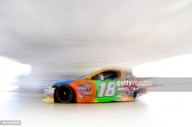 Kyle Busch driver of the MM's Toyota drives through the garage area during practice for the NASCAR Sprint Cup Series Ford EcoBoost 400 at...