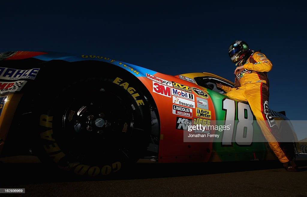 Kyle Busch, driver of the #18 M&M's Toyota, gets into his car during qualifying for the NASCAR Sprint Cup Series Subway Fresh Fit 500 at Phoenix International Raceway on March 1, 2013 in Avondale, Arizona.
