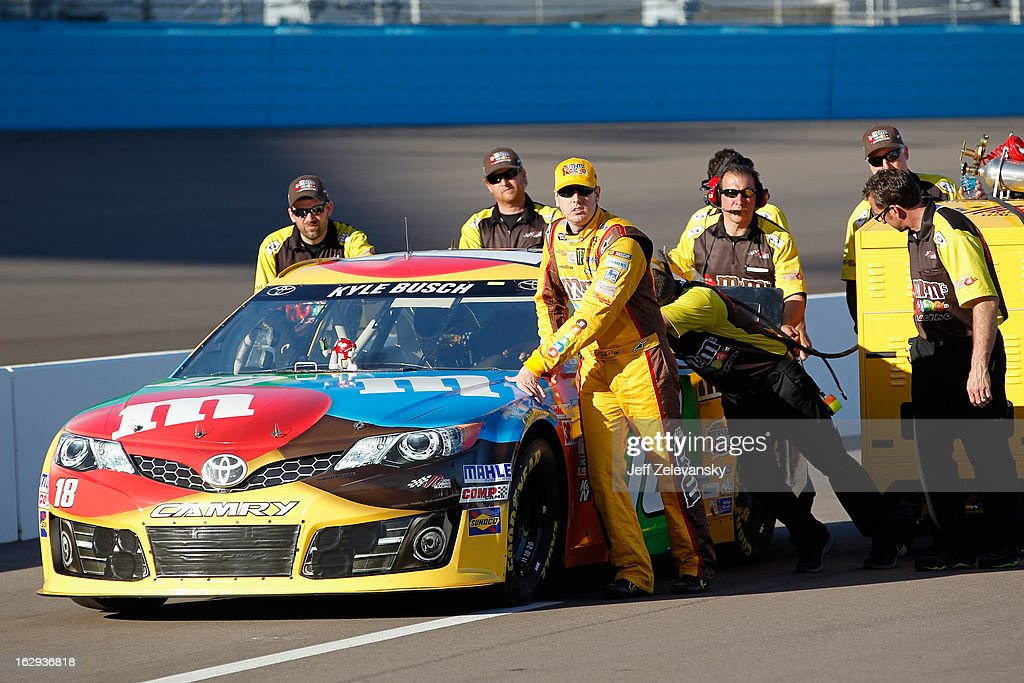 Kyle Busch, driver of the #18 M&M's Toyota, helps push his car on the grid during qualifying for the NASCAR Sprint Cup Series Subway Fresh Fit 500 at Phoenix International Raceway on March 1, 2013 in Avondale, Arizona.