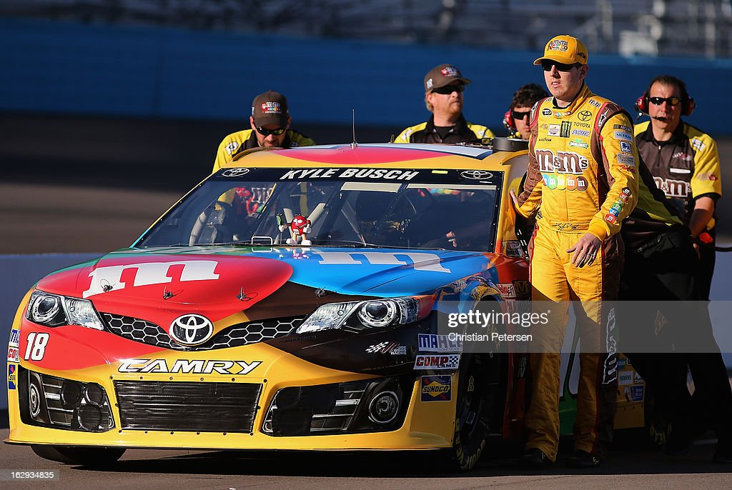 Kyle Busch, driver of the #18 M&M's Toyota, helps push his car out on the grid during qualifying for the NASCAR Sprint Cup Series Subway Fresh Fit 500 at Phoenix International Raceway on March 1, 2013 in Avondale, Arizona.