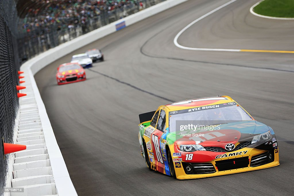 Kyle Busch, driver of the #18 M&M's Toyota, leads a group of cars during the NASCAR Sprint Cup Series STP 400 at Kansas Speedway on April 21, 2013 in Kansas City, Kansas.